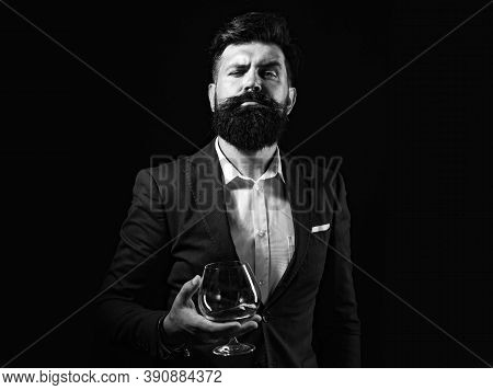Cheerful Bearded Man Is Drinking Expensive Cognac. Confident Well-dressed Man With Glass Of Cognac