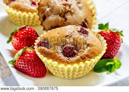 Fresh strawberry muffins with fresh fruit on plate.  Home baked goodness.