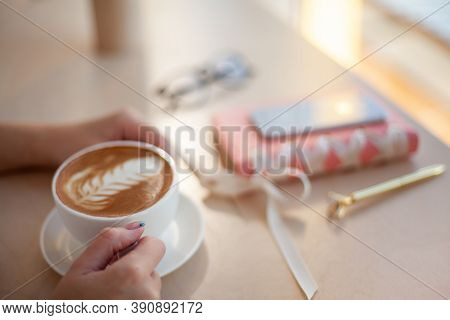 Female Hands Using Mobile Phone For Organising Schedule While Drinking Latte During The Coffee Break