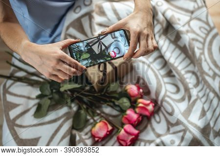 A Womans Hands Are Holding A Mobile Phone And Taking Photos Of Flowers And A Gift Box On A Bedspread