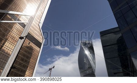 Bottom View Of The Glass Skyscrapers Of The Business District Against Blue Cloudy Sky. Action. Beaut