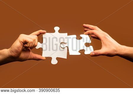 Two Hands Trying To Connect Couple Puzzle. Businessman Hand Connecting Jigsaw Puzzle. Closeup Hands