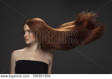 Beautiful Model With Long Smooth, Flying Red Hair Isolated On Dark Grey Studio Background. Young Cau