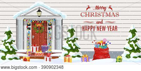 House With Christmas Decorations. Wooden Home Entrance Facade With Xmas Lights, Tree And Gifts On Sn