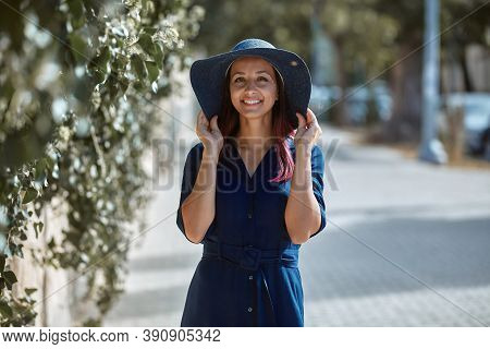 Beautiful Woman In Stylish Hat Posing Near Greenery. Sunny Weather On Nature. Leisure Time And New A