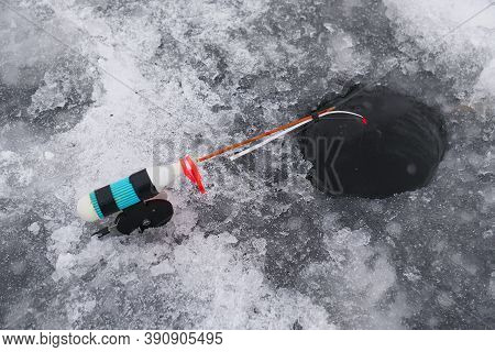 Winter Fishing Rod At The Drilled Hole Catches Fish. Ice Fishing