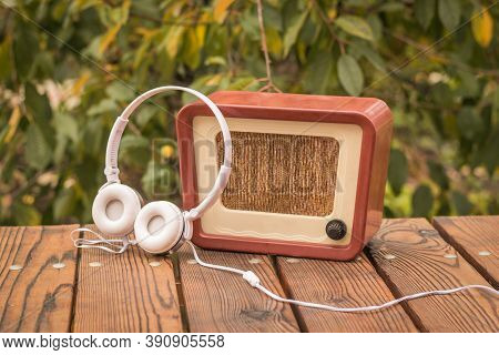 White Headphones Near An Old-fashioned Radio On An Autumn Background. An Old Technique For Listening