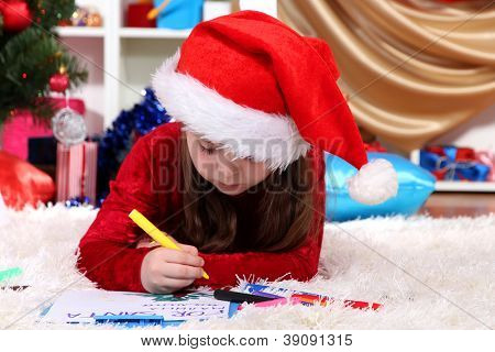 Beautiful little girl writes letter to Santa Claus in festively decorated room poster
