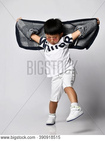 Asian Korean 6-7 Y.o. Kid Boy In Sunglasses White T-shirt And Shorts Dances Gangnam Style Or Makes A