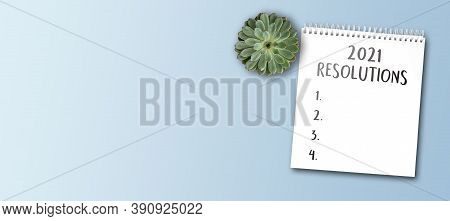 2021 New Years Resolutions And Goals Concept With Notepad On Wide Blue Table Background