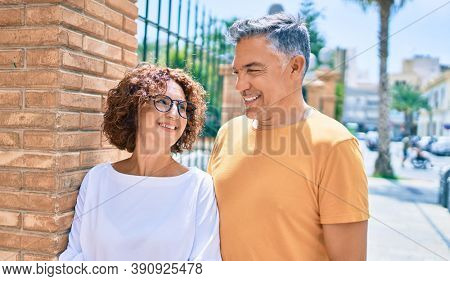 Middle age couple smiling happy leaning on the wall at street of city.