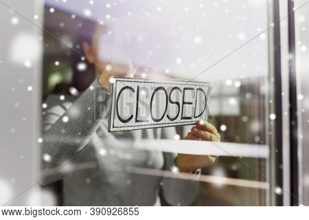 small business, people and service concept - young woman hanging banner with closed word on door or window in winter over snow
