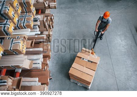 Top View Of Male Worker In Warehouse With Pallet Truck.