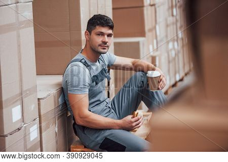 Storage Worker Sits And Have A Break. Eats Sandwitch And Drinks Coffee.