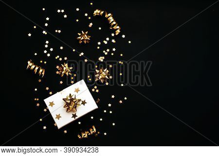 Gift Box And Various Golden Items On A Black Or Dark Background. Festive Conceptual Christmas Or New