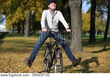Happy mature Caucasian man in casual clothing and bike helmet with raised feet on his city bicycle looking upward in an autumn city park