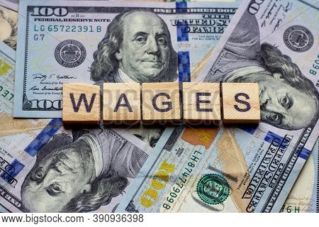 The Word Wages On Dollar Usa Background. Finance And Money Concept.