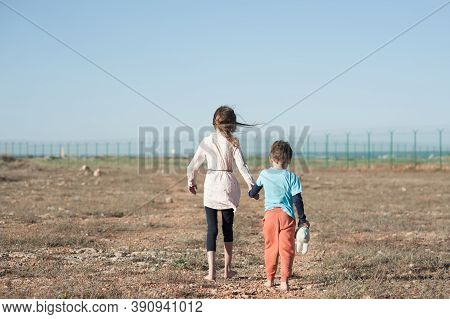 Two Poor Kids Family Brother With Toy And Thin Sister Refugee Illegal Migrant Walking Barefooted Thr