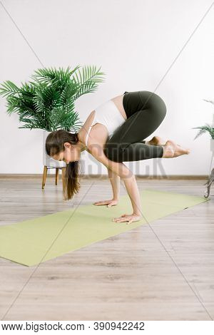 Beautiful Young Fit Caucasian Woman Working Out In The Gym, Doing Exercise Of Yoga Indoor At Home. Y