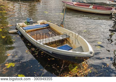 Partially Sunk Small Boat With Outboard Motor. The Photo Was Taken In A Small Dutch Harbor In The Au