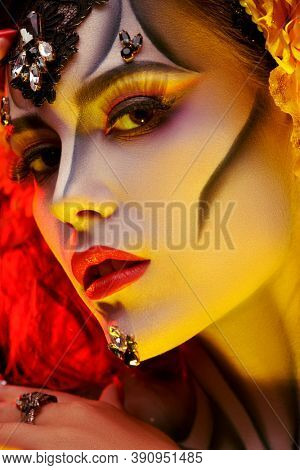 Close-up portrait of Calavera Catrina. Young woman with sugar skull makeup in yellow light. Dia de los muertos. Day of The Dead. Halloween.