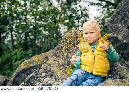 Little Boy Hiking In Mountins, Family Adventure. Little Child Walking In Rocky Green Forest, Smiling