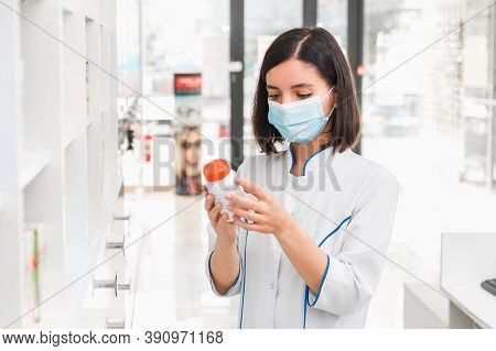 Choosing The Right Medicine. Professional Looking Female Pharmacist With Medical Mask On In Drug Sto