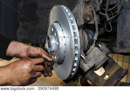 New Brake Disc With An Anti-corrosion Layer, Mounted On The Front Hub, Bolted By A Mechanic.