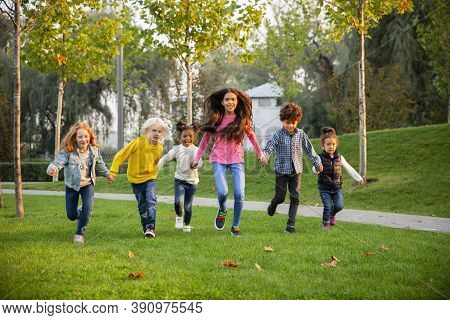 Running. Interracial Group Of Kids, Girls And Boys Playing Together At The Park In Summer Day. Frien