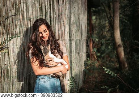 Beautiful Young Girl Holding A Calico Cat, They Look At Each Other. Outdoors Photo, Copy Space