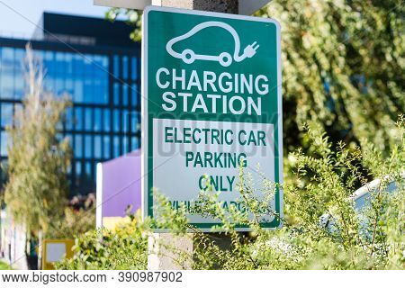 Electric Car Road Sign Charging Station. Outdoor Car Parking And Charging Point For Electric Vehicle