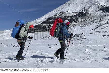 Several Climbers With Large Backpacks And Trekking Poles Walk In Bundles. Mountain Climbing. Trekkin