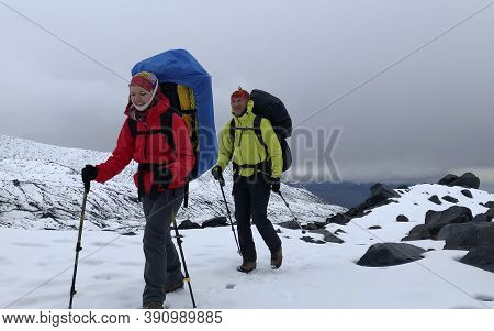 Two Climbers With Large Backpacks And Trekking Poles Are Walking Along The Snowy Trail. Mountain Cli