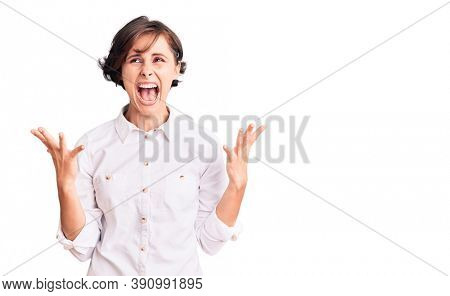 Beautiful young woman with short hair wearing elegant white shirt crazy and mad shouting and yelling with aggressive expression and arms raised. frustration concept.