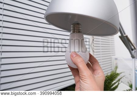 Female Hand Holding A Led Light Bulb To Change, Replace It At Home, Screwing In The Bulb Into A Lamp