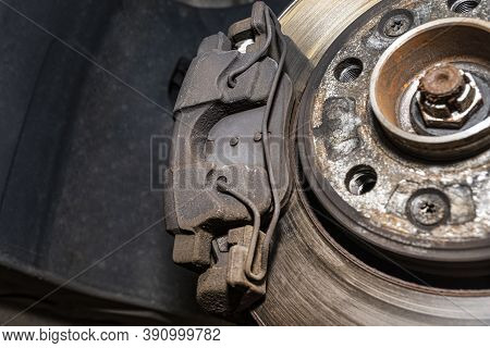 Old Front Brake Disc With Caliper And Brake Pads In The Car, On A Car Lift In A Workshop, Close-up O