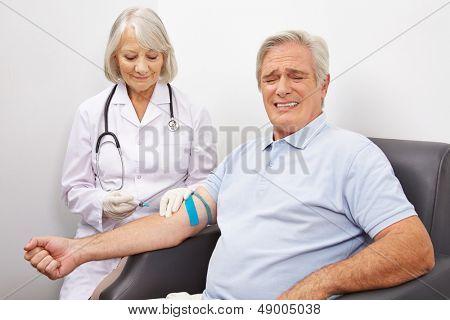 Man making a painful face at immunization shot at a doctors office