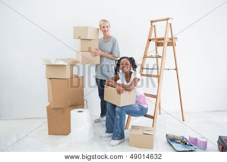 Smiling housemates carrying cardboard moving boxes and looking at camera in new home