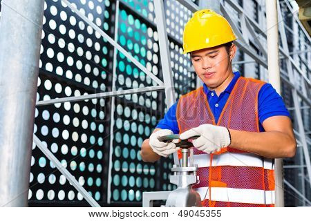 technician or engineer working on a valve on building technical equipment or industrial site