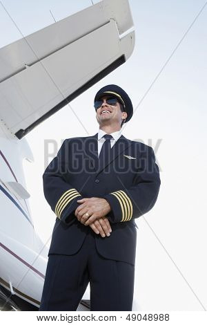 Low angle view of a smiling pilot in uniform standing beside an airplane with hands clasped