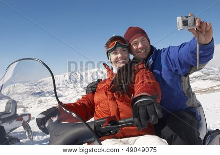 Couple sitting on snowmobile and photographing selves with digital camera in snow