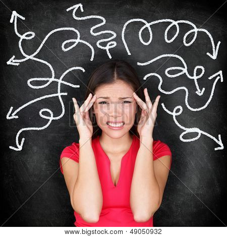 Confused woman - people feeling confusion and chaos. Indecisive, disorientated and bewildered woman stressed with headache over decision making. Girl in 20s on blackboard background. Asian / Caucasian