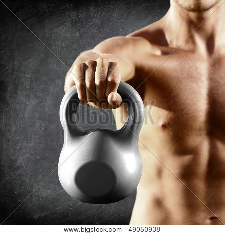 Kettlebell dumbbell - fitness man lifting weight kettle bell training crossfit. Muscular shirtless male torso close up on blackboard background.