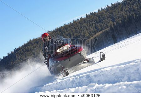 Man snowmobiling through snow in front of forest against blue sky