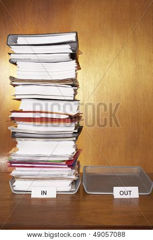 Inbox with stack of paperwork empty outbox on desk