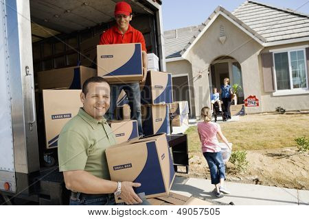 Family and worker unloading delivery van in front of a new house