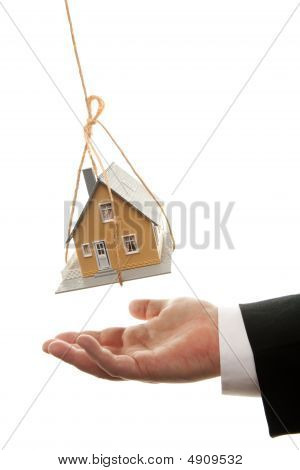 Businessman's Hand Under Dangling House
