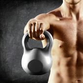 Kettlebell dumbbell - fitness man lifting weight kettle bell training crossfit. Muscular shirtless male torso close up on blackboard background. poster