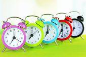 Colorful alarm clocks on table on light background