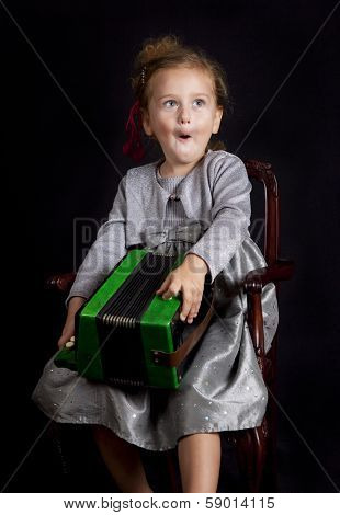 Beautiful young girl with accordion singing on black isolated